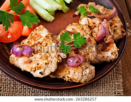 Sliced pork grilled with vegetables on ceramic brown plate. Top view.