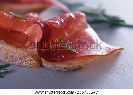 sliced prosciutto with bread with rosemary