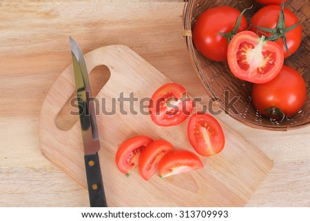 Sliced Tomatoes and knife on wood board for cooking