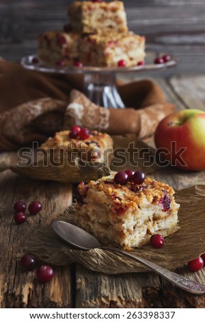 slices of cake with cranberries and fresh berries on the old wooden background. toning in retro style. selective focus
