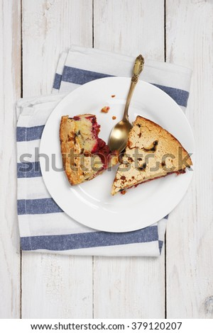 Slices of homemade fruit pie in white plate with kitchen towel on rustic white wooden table. Top view point.