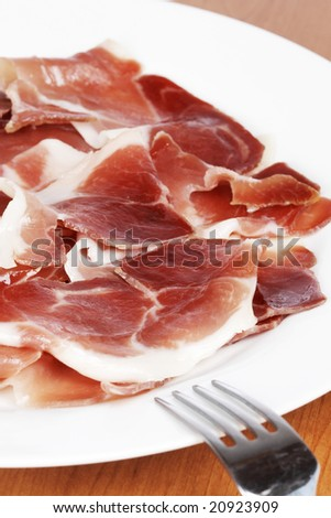 Slices of tasty spanish ham on white dish. Shallow depth of field