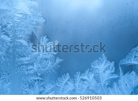 Slightly blurred beautiful frost pattern on a window glass (with copy space for your text), abstract winter background