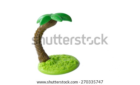 Slightly defocused and close-up shot of plastic coconut palm tree. Concept of vacation getaway or peaceful surrounding. Isolated on white background.