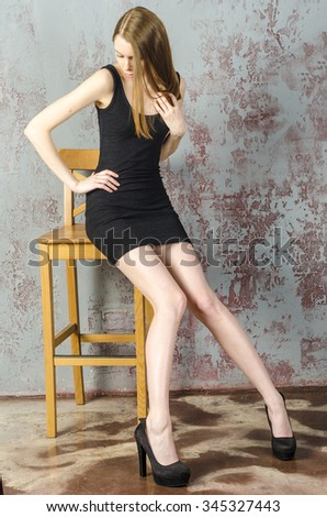 Slim beautiful red-haired girl in a black mini dress with a chair