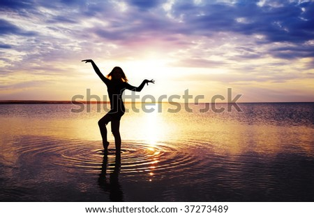 Slim lady standing in the water during sunset