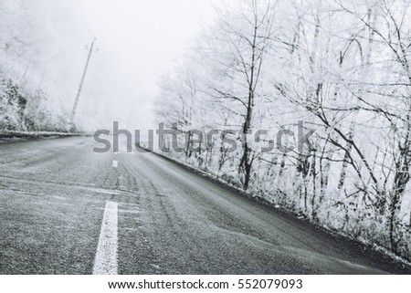 Slippery frozen long asphalt road in white winter forest