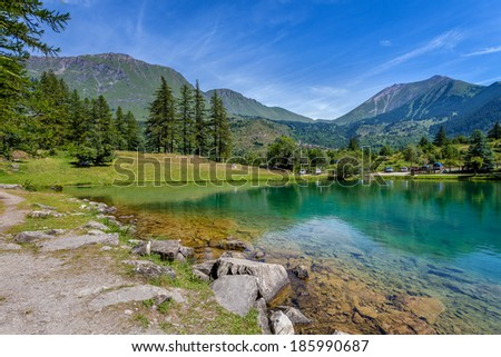 Small alpine lake Laux in the valley among mountains in Alps, Northern Italy.