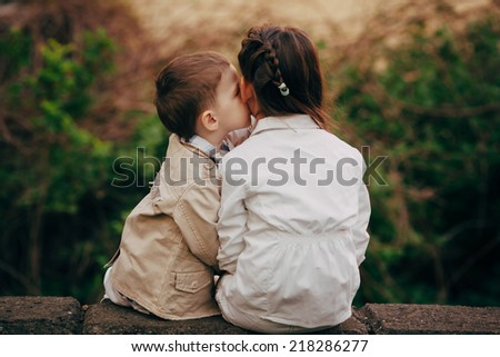 Small and pretty child fell lovely and happy it`s  first kiss