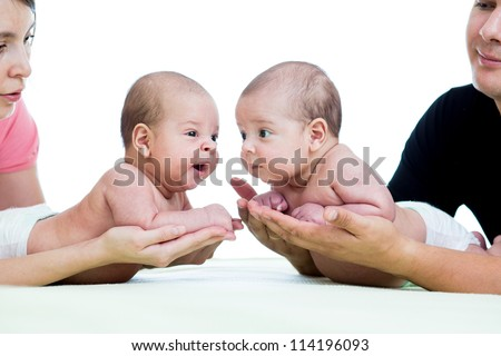 small babies twins on parental hands isolated on white background