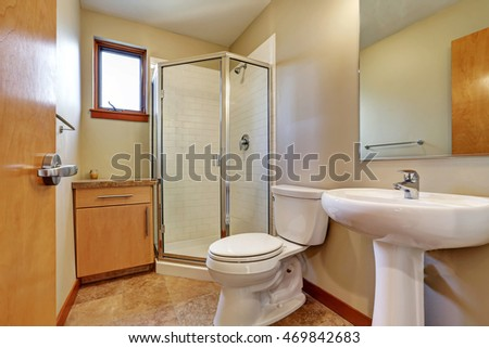 Small bathroom interior with sink, toilet, shower and tile floor. Northwest, USA