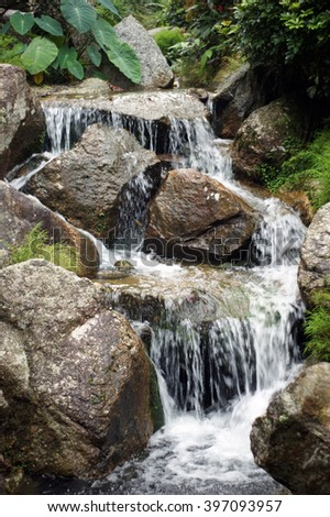 small beautiful stream with brown rocks and cold water
