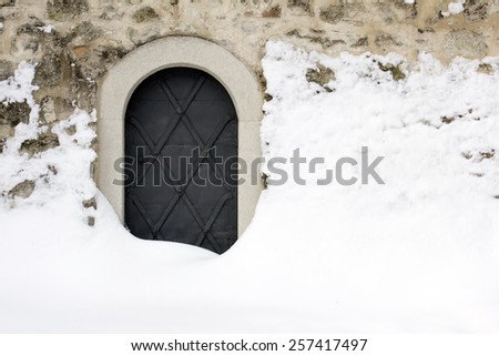 Small black iron castle door, backdoor, covered with snow.