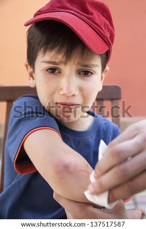 Small boy crying in pain injuring his hand. Father provides first aid