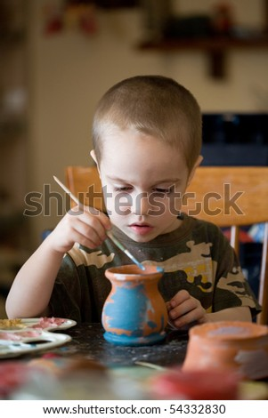 small boy paints the clay jar