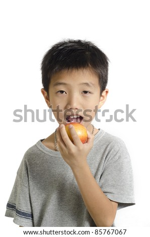 Small boy preparing to bite a big red apple isolated on white background