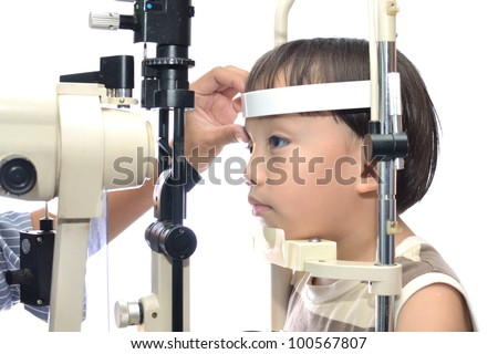 Small boy with slit lamp microscope for eye examination.