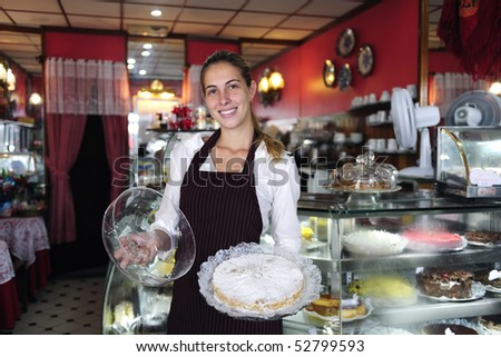 small business: happy waitress showing a tasty cake