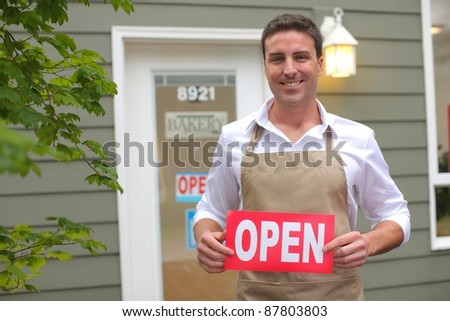 "Small Business owner with ""open"" sign"