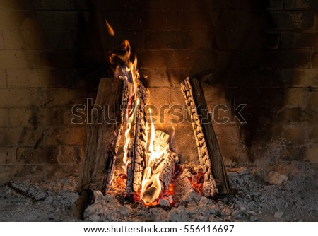 Small campfire lights up inside of brick fireplace