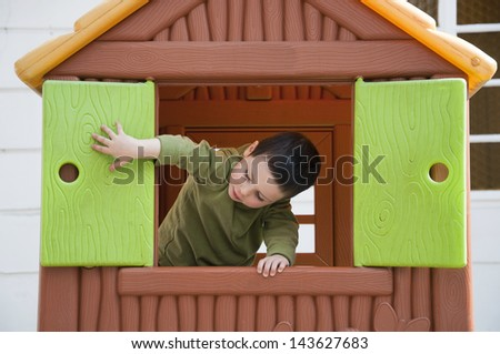 Small child playing with window in a toy playhouse in an yard or an outdoor playground.