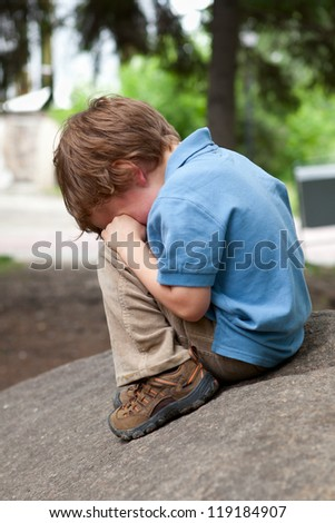 Small child sits on stone in park