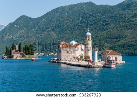 Small church with a bell tower on the island on a background of mountains - Our Lady of the Rocks, Bay of Kotor, Montenegro, Perast town city, Adriatic Sea