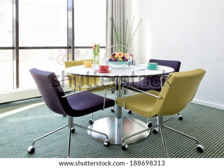 Small Conference Room In Modern Environment With Windows, Round Table And  Colorful Armchairs.