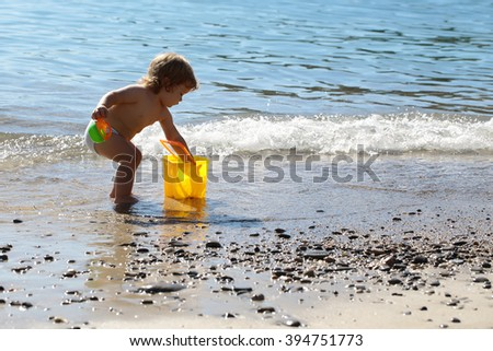 Small curious funny blonde child boy standing on sea coast beach with wavy water sunny day outdoor playing with yellow plastic pail on natural background, horizontal picture