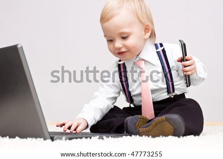 Small cute businessman with cellphone working on laptop
