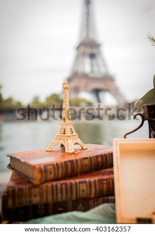 Small decorative Eiffel Tower standing on a vintage books under the real Eiffel Tower in Paris