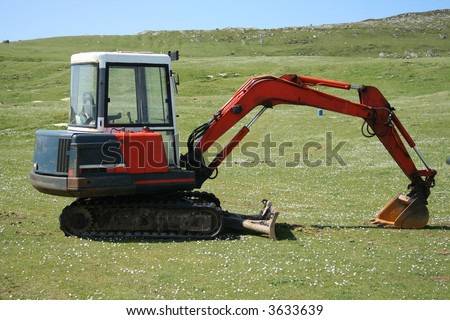 small excavator in green field