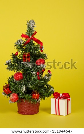 Small fir-tree in a pot with toys and gifts on a yellow background