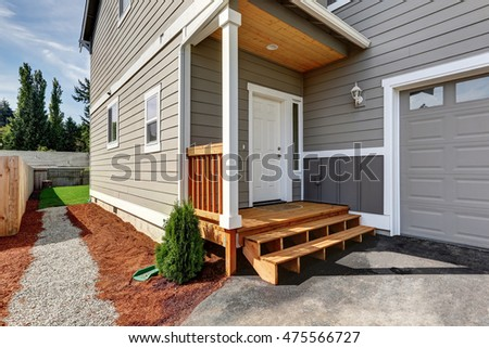 Small front porch with stairs and white entrance door. And gravel walkway to the back yard. Northwest, USA