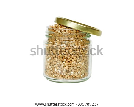 Small glass jar with lots of buckwheat groats on a white background