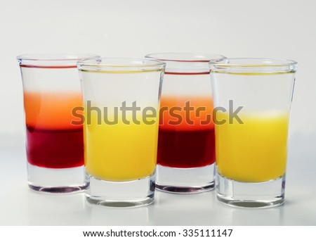 small glass shot glasses with alcohol on a white background.