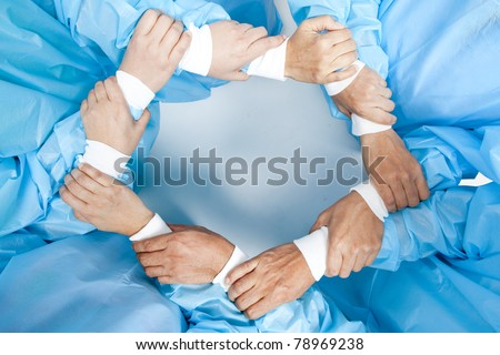 Small group of doctor team joining hands, bird's eyes angle view.