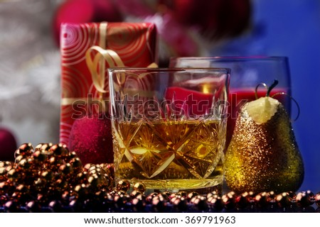 small happy moment of Christmas or New Year`s Eve,a glass of whiskey surrounded by Christmas decoration,toys gifts.