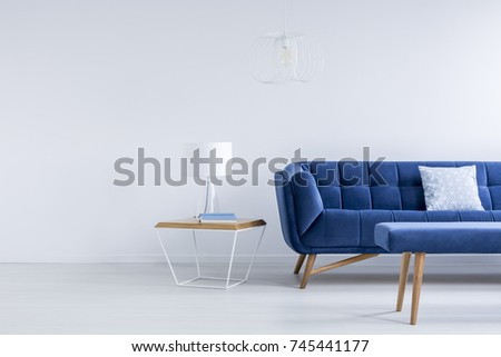 small lamp and book placed on bedside table standing next to royal blue sofa