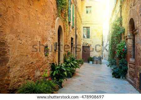 Small Old Mediterranean town - lovely Tuscan street in Pienza with sunshine and flowers, Italy