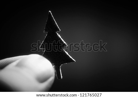Small paper christmas tree in finger. Black and white style. Christmas symbol.