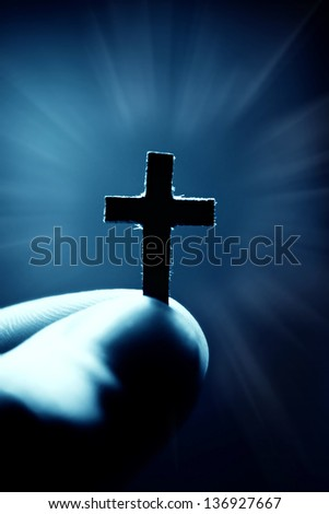 Small paper cross in finger. Faith concept.