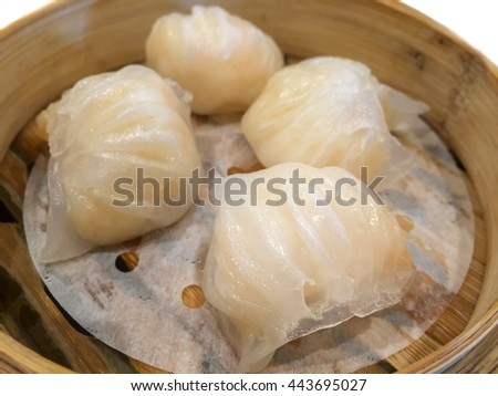 Small piece of Chinese shrimp dumplings (Ha Gao) in hot bamboo basket - close up - isolated with white background
