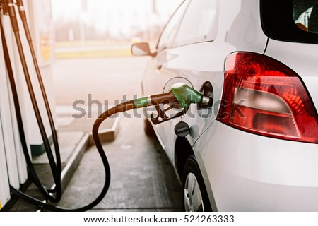 Small silver car refuelling at the gas station