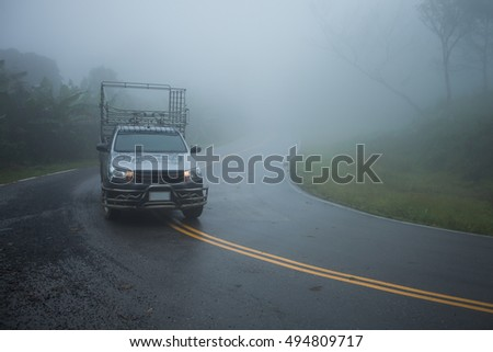 Small truck driving on the foggy 