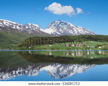 Small village and green hillside on the shore lake, reflection of snowy mountains, sunny day