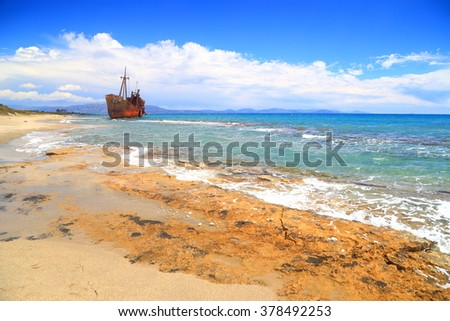 Small waves on Selinitsa beach with distant shipwreck at the horizon, Gythio, Greece