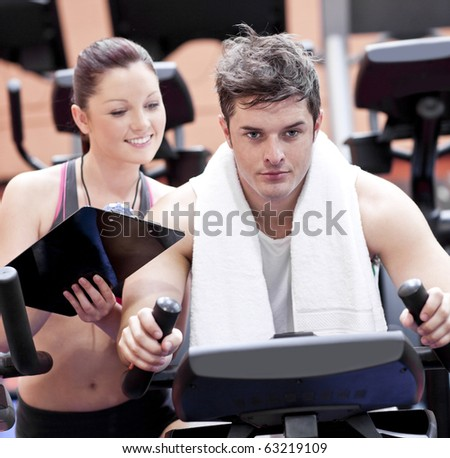 Smart female coach taking notes while her pupil is pedaling on a bicycle in a sport centre