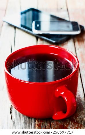 Smart phone  and cup of coffee on old wooden desk. Simple workspace or coffee break in morning/ selective focus.