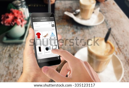 Smart phone online shopping in man hand. Desk with caffe in background. Buy clothes shoes accessories with e commerce web site